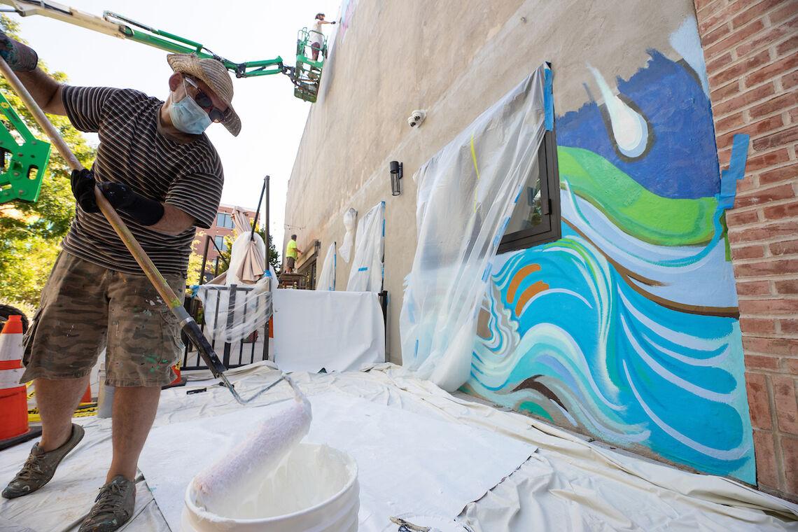 Photo: Artist Paul Santoleri installing the new Pocket Park mural | Steve Weinik